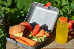 Lunch boxes with food ready to go for work or school, meal preparation or dieting concept. Hamburgers with lettuce. yellow orange. Juice. with banana nuts royalty free stock photos