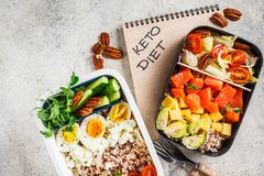 Lunch boxes with keto diet food, top view. Salmon, cheese, eggs and vegetables in food containers