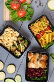 Food container boxes and, raw vegetables, zuchini and eggplants, carrot and onion on grey table stock photo