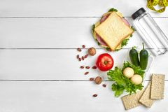 Lunch boxes with sandwich and fresh vegetables, bottle of water, nuts and eggs on white wooden background. Top view with