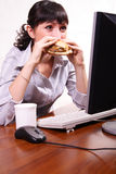 Lunch break. Woman eats a sandwich and looks in the monitor Stock Images