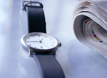 Lunch break. A wrist watcha and a newspaper on a table during a break royalty free stock photo