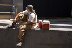 Lunch Break. A North American construction worker takes a lunch break in the midday sun royalty free stock image