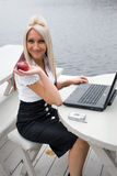 Lunch Break. A beautiful young blonde woman in a mobile business setting eating a red apple royalty free stock photos