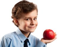 Lunch break with apple. Cute schoolboy having an apple in his lunch break, isolated on white background Stock Photos