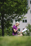 Lunch break with business person eating vegetable in park. Young business woman sitting on grass in park, eating salad for lunch and reading paperwork Stock Images
