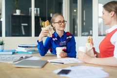 Lunch break. Happy girls with drinks and sandwiches enjoying lunch Royalty Free Stock Images