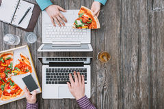 Lunch break at office desk. Business people working at office desk and having a lunch break with a tasty pizza, top view royalty free stock image