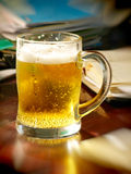 Lunch break-time.Beer glass on table with notebooks. Royalty Free Stock Photography