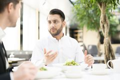 Lunch in cafe. Young manager and his colleague sitting by served table in cafe, having business lunch and discussing some working problems Stock Image