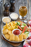 Lunch with chicken nuggets, french fries, salad and beer Stock Photo