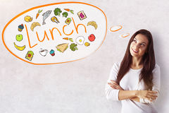 Lunch concept. Attractive smiling young woman dreaming of food on concrete background. Lunch concept stock photo