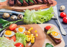 Lunch with croutons. Tapas, parsley sprigs, quail eggs in shell and fried eggs, lettuce, cherry tomatoes, corn grains on dark wooden background stock image