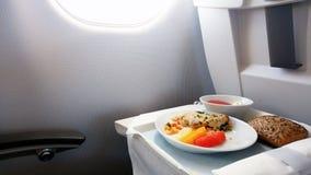 Lunch in de commerciële klasse aan boord van de vliegtuigen stock afbeeldingen