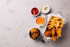Lunch or dinner - chicken strips, french fries, corn and dips. Lunch or dinner - fried chicken strips, french fries, roasted corn and dips. Food captured from stock photo
