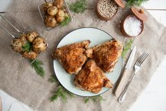 Baked chicken thighs lying on a wooden board with greens and baby potato. Lunch or dinner idea: Baked chicken thighs lying on a wooden board with greens and baby royalty free stock photos