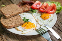 Lunch,Dinner,Supper. Breakfast or dinner or lunch with eggs bacon and a few tomatoes Royalty Free Stock Images