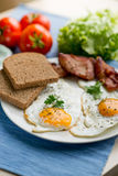 Lunch,Dinner,Supper. Breakfast or dinner or lunch with eggs bacon and a few tomatoes Royalty Free Stock Image