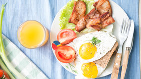Lunch,Dinner,Supper. Breakfast or dinner or lunch with eggs bacon and a few tomatoes Stock Photos