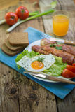 Lunch,Dinner,Supper. Breakfast or dinner or lunch with eggs bacon and a few tomatoes Stock Photo