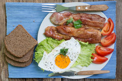 Lunch,Dinner,Supper. Breakfast or dinner or lunch with eggs bacon and a few tomatoes Stock Images
