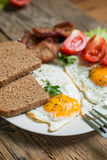 Lunch,Dinner,Supper. Breakfast or dinner or lunch with eggs bacon and a few tomatoes Royalty Free Stock Photos