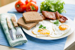 Lunch,Dinner,Supper. Breakfast or dinner or lunch with eggs bacon and a few tomatoes Stock Image