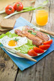 Lunch,Dinner,Supper. Breakfast or dinner or lunch with eggs bacon and a few tomatoes Royalty Free Stock Photo