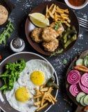 Lunch- eller mellanmåltabell - stekte ägg, fega bollar, potatischiper, grönsaker, såser på en mörk bakgrund Lantlig stil, bästa s arkivbilder
