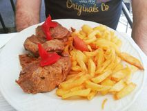 Meat with chips and red pepper stock photography