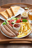 Lunch with grilled sausages, French fries, fresh vegetables Stock Photography