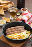 Lunch with grilled sausages, French fries, toast and beer Stock Photo