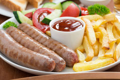 Lunch with grilled sausages, French fries, vegetables and beer Stock Photos