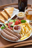 Lunch with grilled sausages with French fries, vegetables Stock Photos