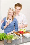 Lunch happy couple cook salad enjoy wine. In kitchen Royalty Free Stock Images