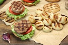 Lunch With Homemade BBQ Grilled Hamburgers On The Picnic Table Royalty Free Stock Images