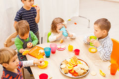 Lunch in kindergarden. Children are sitting at the table with lunch and eating fruits and cakes Royalty Free Stock Photos