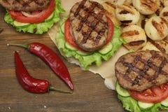 Lunch med hemlagade BBQ grillade hamburgare på picknicktabellen Arkivfoto