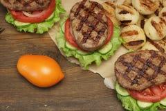 Lunch med hemlagade BBQ grillade hamburgare på picknicktabellen Royaltyfria Foton