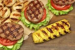 Lunch med hemlagade BBQ grillade hamburgare på picknicktabellen Royaltyfri Bild