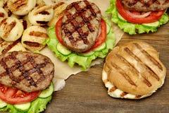 Lunch med hemlagade BBQ grillade hamburgare på picknicktabellen Fotografering för Bildbyråer