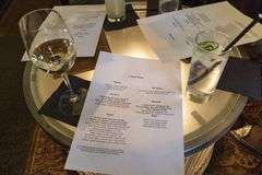 Lunch menus and drinks on a round table. Menu with drinks glasses on an illuminated round table in a restaurant Stock Photo
