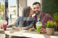 Lunch with my girlfriend. Good looking young men having a healthy lunch with his girlfriend and getting kissed in the cheek Royalty Free Stock Image