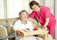 Lunch at the Nursing Home. Friendly nurse brings a mean to an elderly shut-in. Could also be lunch time at the nursing home royalty free stock images