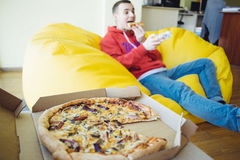 Lunch in office - man sitting with feet on the table, suffering from overeating Stock Image