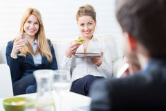 Lunch at the office. Two happy businesswomen eating lunch at the office Royalty Free Stock Image