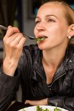 Businesswoman eating salad in an outdoor cafe. Healthy lifestyle: girl eating green tasty food Royalty Free Stock Image