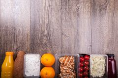 Lunch packed in different boxes. Close up of lunch packed in different boxes. Fresh and healthy eating on wooden background Royalty Free Stock Images