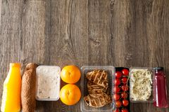 Lunch packed in different boxes. Fresh and healthy eating on wooden background Stock Photo