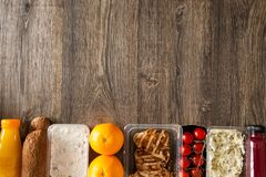 Lunch packed in different boxes. Fresh and healthy eating on wooden background Royalty Free Stock Images
